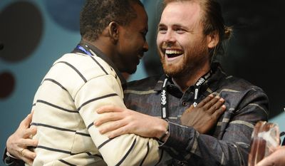 """Cutter Hodierne, right, director of """"Fishing Without Nets,"""" is embraced by cast member Abdikani Muktar after winning the Directing Award: Dramatic for his film during the 2014 Sundance Film Festival Awards Ceremony on Saturday, Jan. 25, 2014, in Park City, Utah. (Photo by Chris Pizzello/Invision/AP)"""