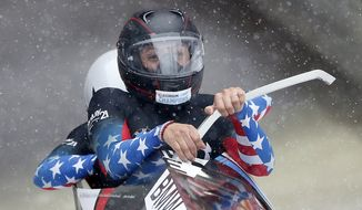 Second placed Elana Meyers, foreground, and Aja Evans of the United States start their first run of the two-woman Bobsled World Cup race in Koenigssee, southern Germany, on Sunday, Jan. 26, 2014. (AP Photo/Matthias Schrader)