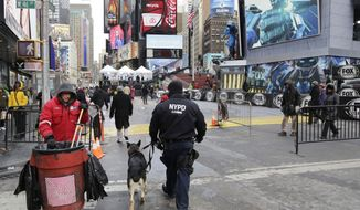 An NYPD officer patrols with a dog, Sunday, Jan. 26, 2014 in New York's Times Square. A dozen blocks of Broadway, in the heart of Manhattan, will close to traffic for four days so the NFL can host a Super Bowl festival. The championship football game between the Denver Broncos and Seattle Seahawks is Sunday, Feb. 3 in East Rutherford, N.J. (AP Photo/Mark Lennihan)