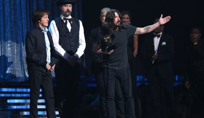 "Paul McCartney, from left, Krist Novoselic and Pat Smear, partially obscured, listen as Dave Grohl, foreground, accepts the award for best rock song for ""Cut Me Some Slack"" at the 56th annual Grammy Awards at Staples Center on Sunday, Jan. 26, 2014, in Los Angeles. (Photo by Matt Sayles/Invision/AP)"