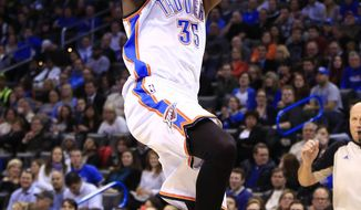 Oklahoma City Thunder forward Kevin Durant (35) shoots over Atlanta Hawks forward DeMarre Carroll during the fourth quarter of an NBA basketball game, Monday, Jan. 27, 2014, in Oklahoma City. Oklahoma City won 111-109. (AP Photo/Alonzo Adams)