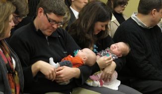 Andrew Marske, left, and his wife, Kelsey, hold their 6-week-old twins, Arthur and Augusta, as the Kansas Senate Public Health and Welfare Committee considers a bill voiding surrogate mother contracts, Monday, Jan. 27, 2014, at the Statehouse in Topeka, Kan. A friend carried and gave birth to their twins for them. (AP Photo/John Hanna)