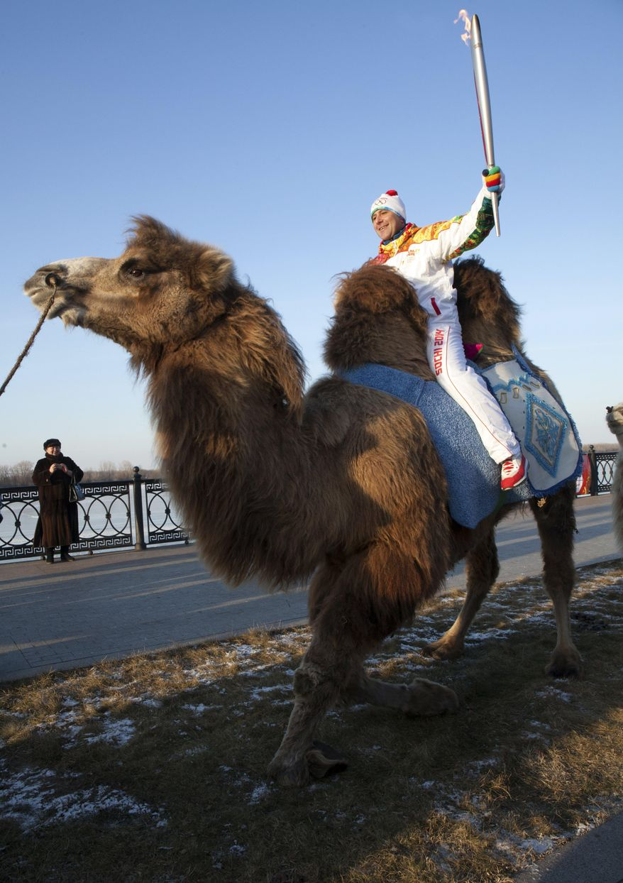 In this photo taken on Sunday, Jan.  26, 2014 and provided by Olympictorch2014.com, an Olympic torch bearer Dmitry Slaschev, top, rides a camel holding an Olympic torch during the torch relay in  the southern Russian city of Astrakhan.  The relay for the Sochi Winter Games, which began on Oct. 7, 2013 in Moscow, will pass through many cities that showcase the historical, cultural and ethnic richness of Russia. (AP Photo/Olympictorch2014.com)