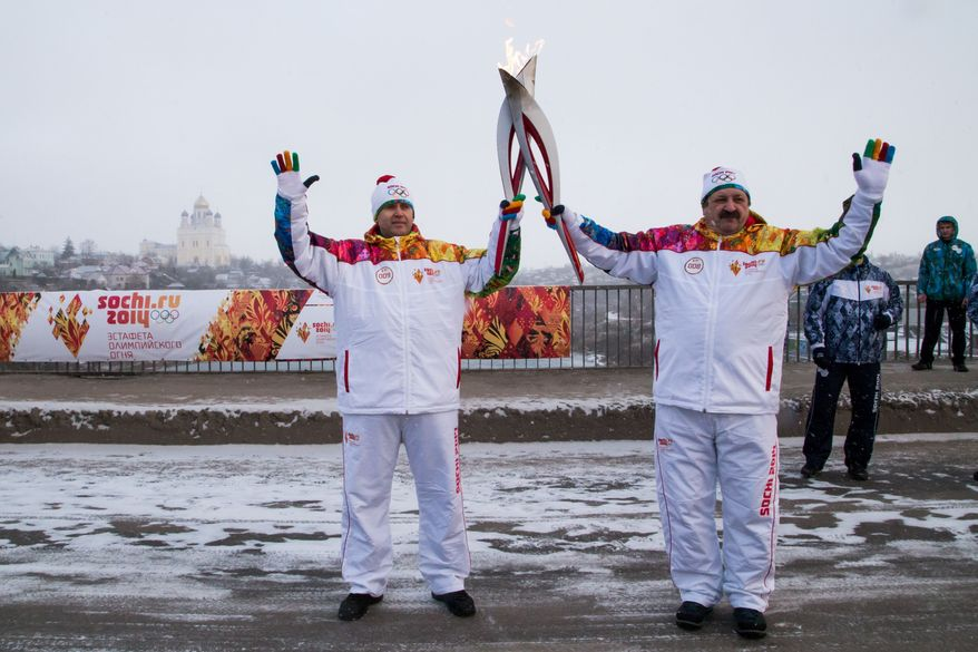 In this photo provided by Olympictorch2014.com, torch bearers pose with Olympic torches during the Olympic torch relay in Yelets, some 380 kilometers (237.5 miles) south of Moscow, Russia, Tuesday, Jan. 14, 2014. The 65,000-kilometer (40,389 mile) Sochi torch relay, which started on Oct. 7, is the longest in Olympic history. The torch has traveled to the North Pole on a Russian nuclear-powered icebreaker and has even been flown into space. (AP Photo/Olympictorch2014.com)