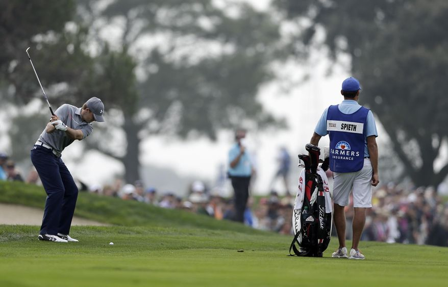 Jordan Spieth, left, hits his second shot on the second hole of the South Course at Torrey Pines during the final round of the Farmers Insurance Open golf tournament Sunday, Jan. 26, 2014, in San Diego. (AP Photo/Gregory Bull)