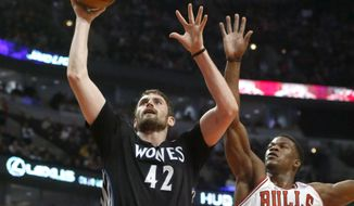 Minnesota Timberwolves forward Kevin Love (42) scores past Chicago Bulls guard Jimmy Butler (21) during the first half of an NBA basketball game, Monday, Jan. 27, 2014, in Chicago. (AP Photo/Charles Rex Arbogast)