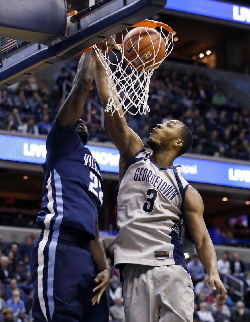 Villanova forward JayVaughn Pinkston, left, dunks the ball over Georgetown forward Mikael Hopkins (3) during the first half of an NCAA college basketball game, Monday, Jan. 27, 2014, in Washington. (AP Photo/Alex Brandon)