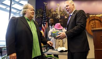 Seattle Mayor Ed Murray, right, carefully lifts a glass bowl as the artist, Dale Chihuly, looks on after Murray spoke via speakerphone with Denver Mayor Michael Hancock announcing what is at stake in their bet on the success of their football teams in the Super Bowl XLVIII, Monday, Jan. 27, 2014, in Seattle. Murray said in the unlikely event of a Denver Broncos win on Sunday, he would send Hancock salmon, Dungeness crab, a handmade bicycle custom-painted in Seattle Seahawks livery made by Rodriguez Bicycles in Seattle and a piece of blown glass by Chihuly. If the Seahawks win, Hancock says he'll send a sampling of Denver's green chile and a hoodie, ball cap and skis handmade by Denver's locally grown Icelantic Skis. (AP Photo/Elaine Thompson)