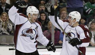Colorado Avalanche center Paul Stastny, left, and Tyson Barrie (4) celebrate a power play goal by Stastny against the Dallas Stars in the second period of an NHL hockey game, Monday, Jan. 27, 2014, in Dallas. (AP Photo/Tony Gutierrez)