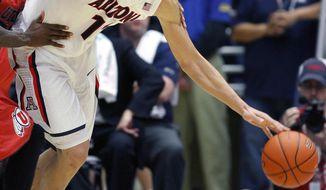 Arizona's Aaron Gordon (11) struggles with Utah's Delon Wright, left, as he drives toward the basket in the second half of an NCAA college basketball game on Sunday, Jan. 26, 2014, in Tucson, Ariz. (AP Photo/John Miller)
