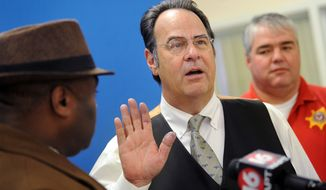 Comedian, singer and actor Dan Aykroyd, center, is sworn in as a reserve deputy of the Hinds County Mississippi Sheriff's Department by Sheriff Tyrone Lewis, left, during a ceremony at department headquarters in Jackson, Miss., on Friday, Jan. 24, 2014. Standing at right is Hinds County Chief Deputy Chris Picou. (AP Photo/The Clarion-Ledger, Joe Ellis)