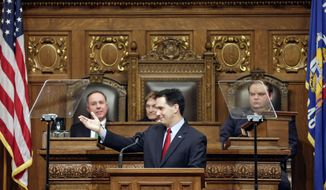 FILE - Wisconsin Gov. Scott Walker acknowledges guests during his State of the State address to a joint session of the Legislature in the Assembly chambers at the state Capitol Wednesday, Jan. 22, 2014, in Madison, Wis. Walker made the case in his State of the State speech Wednesday that extra money collected thanks to an improving national economy should be returned as property and income tax cuts, even as some Republicans are saying his proposal goes too far.  (AP Photo/Andy Manis)
