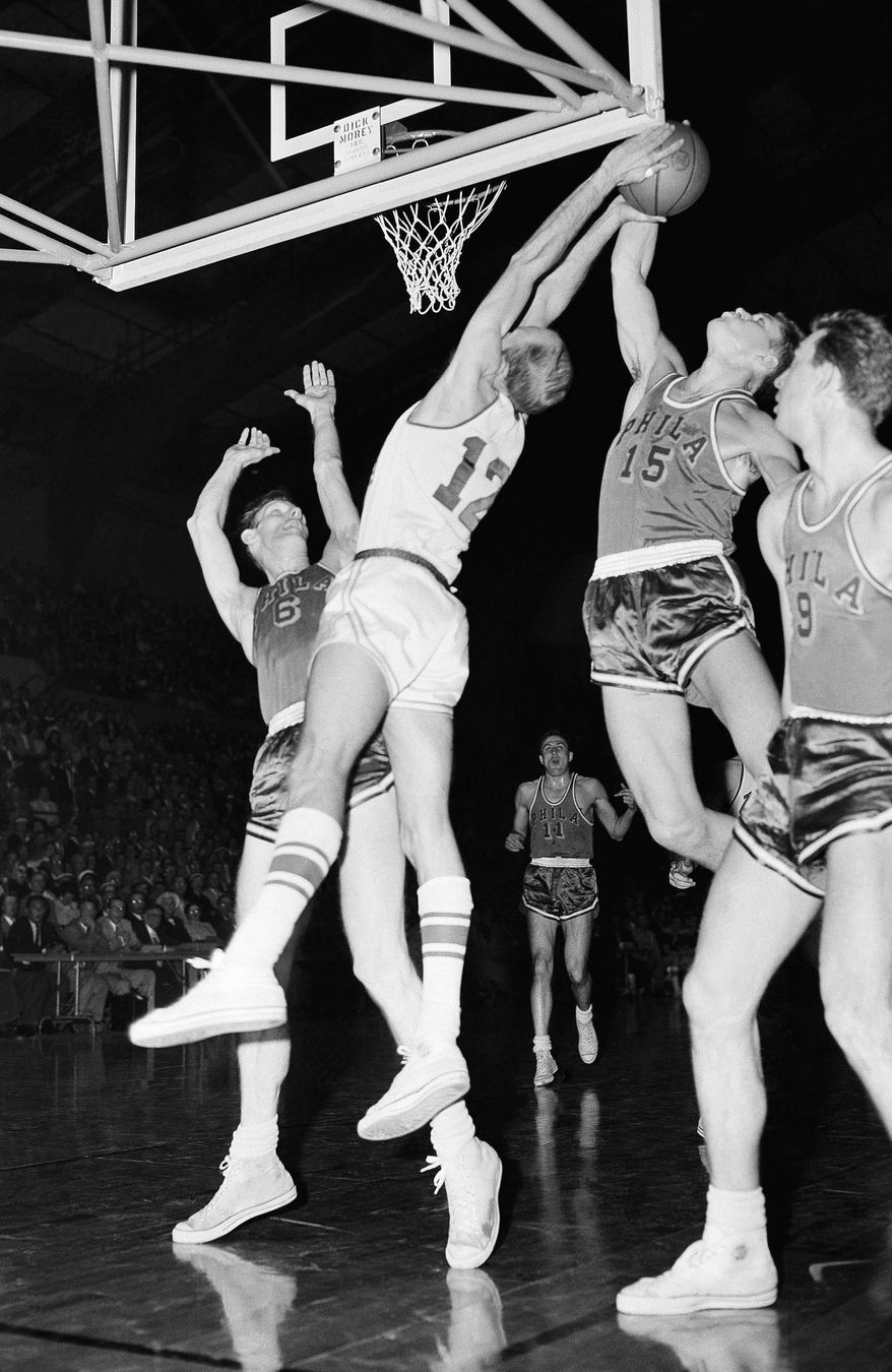 File-This April 2, 1956, file photo shows George Yardley (12) Fort Wayne outreaching Tom Gola (15) of the Philadelphia Warriors, under his own basket to save the ball for the Pistons in Fort Wayne. Gola, the Hall of Fame basketball player who led La Salle to the 1954 NCAA title and helped the Philadelphia Warriors win the 1956 NBA championship, died Sunday Jan. 26, 2014. He was 81. (AP Photo/File)