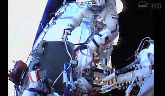 In an image made from NASA TV,  the helmet camera  of flight engineer Sergey Ryazanskiy shows commander Oleg Kotov Monday Jan. 27, 2014, as they install a high-resolution camera outside the International Space Station.  Ryaazansky's gloved hand is at lower left.  Kotov and Ryazanskiy made the spacewalk  to install a pair of commercially provided cameras.  (AP Photo/NASA)