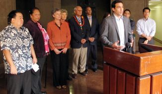 Rep. Chris Lee speaks to journalists from a lectern at the Hawaii Capitol in Honolulu on Monday, Jan. 27, 2014. Lee is one of several lawmakers suggesting any fines or settlements the state collects for ocean spills be put toward restoring coral reefs. (AP Photo/Oskar Garcia)