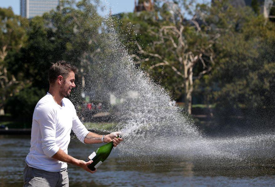 Switzerland's Stanislas Wawrinka sprays champagne as he celebrates his Australian Open men's singles final win over Spain's Rafael Nadal on Sunday evening in Melbourne, Australia, Monday, Jan. 27, 2014. (AP Photo/Aaron Favila)