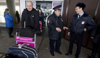 Visitors arrive in Sochi airport, Russia, Monday, Jan. 27, 2014 as police officers talk aside. Russia has spent about $51 billion to deliver the Winter Olympics in Sochi, which run Feb. 7-23. (AP Photo/Pavel Golovkin)