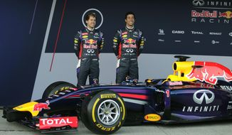 Infiniti Red Bull Racing drivers Sebastian Vettel of Germany, left, and Daniel Ricciardo of Australia, right, attend the launch of their new RB10 Formula One car at the Circuito de Jerez on Tuesday,  Jan. 28, 2014, in Jerez de la Frontera, Spain. (AP Photo/Miguel Angel Morenatti)