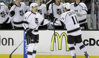 Los Angeles Kings' Anze Kopitar (11), of Slovenia, celebrates with teammates on the bench after scoring against the San Jose Sharks during the second period of an NHL hockey game on Monday, Jan. 27, 2014, in San Jose, Calif. (AP Photo/Marcio Jose Sanchez)
