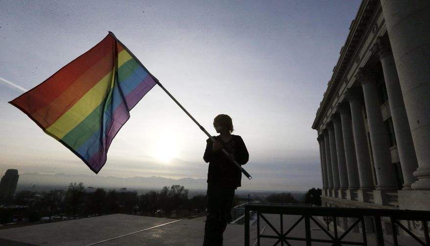 **FILE** Corbin Aoyagi, a supporters of gay marriage, waves his flag during a rally at the Utah State Capitol, Tuesday, Jan. 28, 2014, in Salt Lake City. Opponents and supporters of gay marriage held twin rallies at the Capitol on Tuesday. More than 1,000 gay couples rushed to get married when a federal judge overturned Utah's constitutional amendment banning same-sex marriage in late December 2013. In early January the U.S. Supreme Court granted Utah's request for an emergency halt to the weddings. (AP Photo/Rick Bowmer)