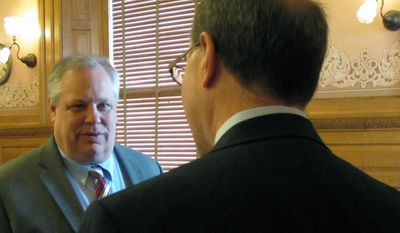 Tom Witt, left, executive director of the gay-rights group Equality Kansas, confers with Kansas state Rep. Steve Brunk, a Wichita Republican, before a committee hearing on gay marriage issues, Tuesday, Jan. 28, 2014, at the Statehouse in Topeka, Kan. Brunk is chairman of the committee hearing a bill that Witt and his group opposes. (AP Photo/John Hanna)