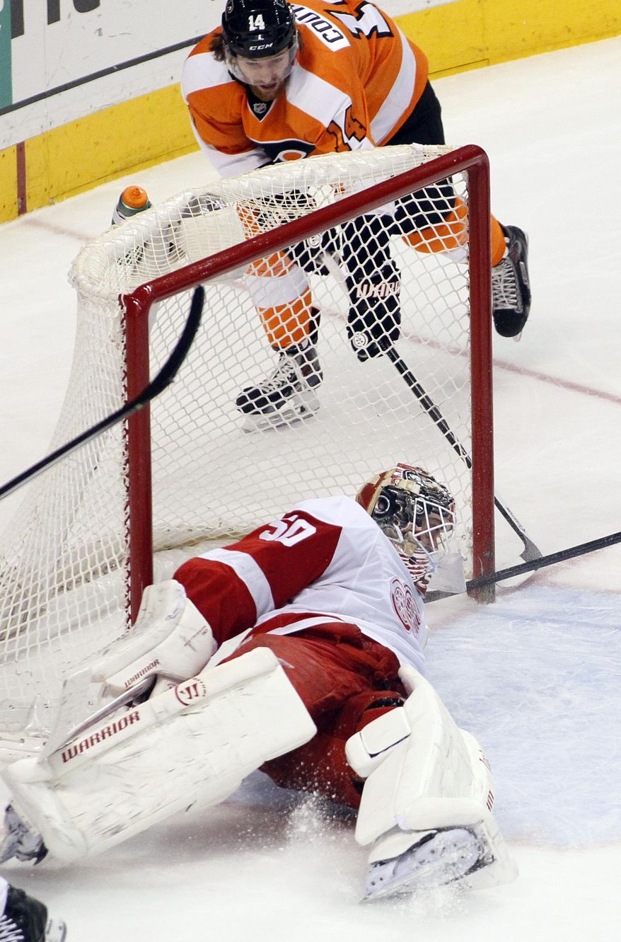 Detroit Red Wings goalie Jonas Gustavsson lays in the crease trying to block the goal scored by Philadelphia Flyers' Sean Couturier, behind him, during the third period of an NHL hockey game, Tuesday, Jan. 28, 2014, in Philadelphia. The Flyers won 5-0. (AP Photo/Tom Mihalek)