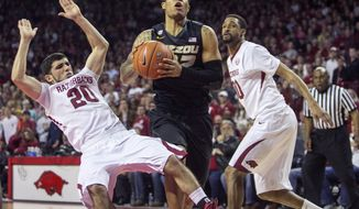 Missouri guard Jabari Brown (32) drives to the hoop as Arkansas guard Kikko Haydar (20) is taken to the ground during the second half of an NCAA college basketball game on Tuesday, Jan. 28, 2014, in Fayetteville, Ark. Brown led with 24 points as Missouri defeated Arkansas 75-71. (AP Photo/Gareth Patterson)