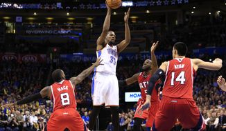 Oklahoma City Thunder forward Kevin Durant (35) looks to pass as Atlanta Hawks forward DeMarre Carroll (5) and Gustavo Ayon (14) and Shelvin Mack (8) defend during the fourth quarter of an NBA basketball game, Monday, Jan. 27, 2014, in Oklahoma City. Oklahoma City won 111-109. (AP Photo/Alonzo Adams)
