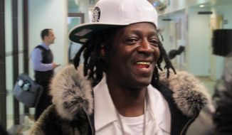 Flavor Flav speaks with reporters following an appearance in Nassau County District Court in Hempstead, N.Y., on Tuesday, Jan. 28, 2014. The rapper, whose real name is William Drayton, was in court on charges he was speeding and driving with a suspended license en route to his mother's funeral in Long Island on Jan. 9. Drayton pleaded not guilty Tuesday and was released without bail. (AP Photo/Frank Eltman)