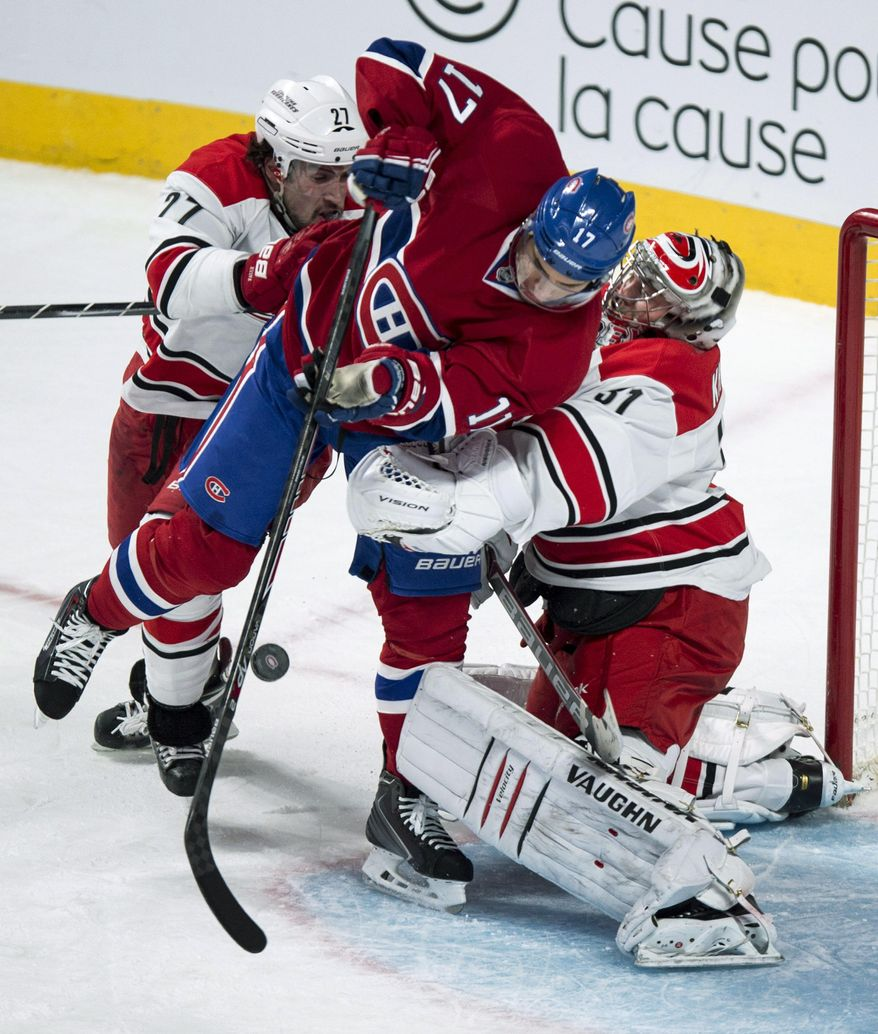 Montreal Canadiens' Rene Bourque gets caught between Carolina Hurricanes goalie Anton Khudobin and defenseman Justin Faulk during the second period of an NHL hockey game Tuesday, Jan. 28, 2014, in Montreal. (AP Photo/The Canadian Press, Paul Chiasson)