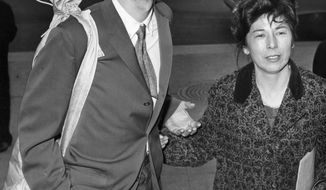 FILE - In this April 4, 1961 file photo, Pete Seeger, with a banjo slung over his shoulder, is accompanied by his wife, Toshi, as he arrives at the federal court in New York for sentencing on a conviction for contempt of Congress. He was given a one-year sentence for refusing to answer questions about possible Communist affiliations. Before he was sentenced, Seeger asked Judge Thomas F. Murphy for permission to sing a song. The judge declined. The sentence was eventually overturned on appeal. (AP Photo)