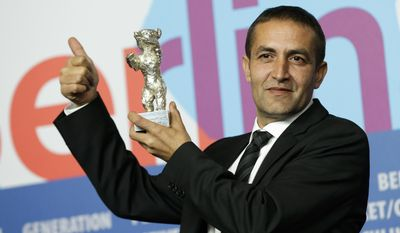 FILE - In this Feb. 16, 2013 file photo actor Nazif Mujic holds up his Silver Bear Best Actor award for his role in 'An Episode In the Life of an Iron Picker' at the 63rd edition of the Berlinale, International Film Festival in Berlin, Germany. Mujic, a Roma from a tiny village in Bosnia, won the Silver Bear award in 2013. Now, almost a year later, the movie star has turned into an asylum seeker.  Mujic is back in Berlin, but this time he came with his family to apply for asylum, was rejected by the German authorities and is desperately fighting his deportation back to Bosnia in March. (AP Photo/Markus Schreiber, File)