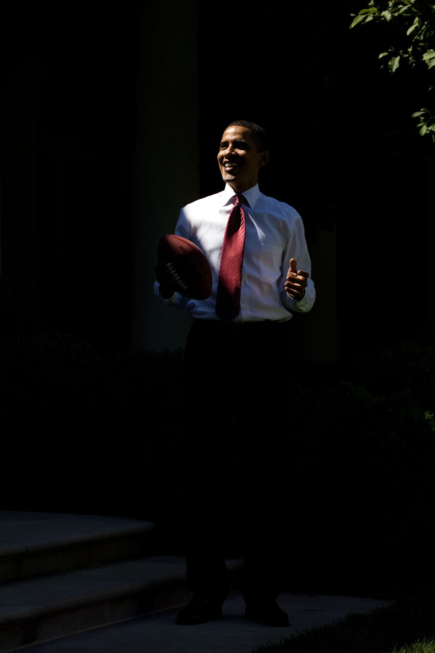 President Barack Obama stands in a shaft of light while playing football outside the Oval Office May 20, 2009.  (Official White House photo by Pete Souza.)  This official White House photograph is being made available for publication by news organizations and/or for personal use printing by the subject(s) of the photograph. The photograph may not be manipulated in any way or used in materials, advertisements, products, or promotions that in any way suggest approval or endorsement of the President, the First Family, or the White House.