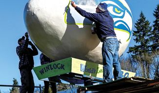 """Painters Ron Gaul, right, and his son Mason Gaul, are giving the """"World's Largest Egg"""" in Winlock, Wash., on Jan. 25, 2014.  The Seattle Seahawks will face the Denver Broncos this Sunday at Super Bowl XLVIII this Sunday.  (AP Photo/The Daily News, Bill Wagne )"""