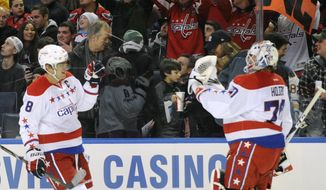 Washington Capitals'  Alex Ovechkin (8) of Russia, celebrates his second goal with Braden Holtby (70) and Washington fans during the first period of an NHL hockey game against the Buffalo Sabres in Buffalo, N.Y., Tuesday, Jan. 28, 2014. (AP Photo/Gary Wiepert)