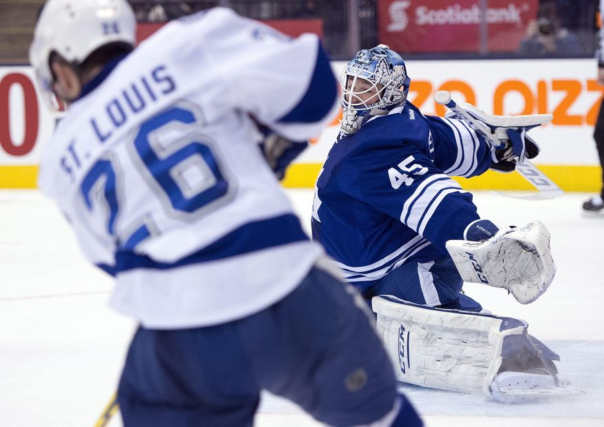 Toronto Maple Leafs goaltender Jonathan Bernier, right, makes a save on Tampa Bay Lightning right winger Martin St. Louis during the third period of an NHL hockey game in Toronto, Tuesday, Jan. 28, 2014. (AP Photo/The Canadian Press, Frank Gunn)
