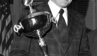 FILE - In this Feb. 5, 1973, file photo, University of Pennsylvania football coach Harry Gamble holds his trophy presented by the Football Writers Association of New York in New York. Gamble, who coached the Philadelphia Eagles as well as Lafayette, Penn and New Jersey high school teams before retiring as the Eagles' president, died Tuesday, Jan. 28, 2014, the Eagles said in a statement. He was 83. (AP Photo/John J. Lent, File)