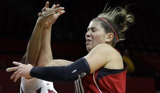 Rutgers guard Briyona Canty (4) blocks a shot by Louisville forward Sara Hammond (00) during the first half of an NCAA college basketball game Tuesday, Jan. 28, 2014, in Piscataway, N.J. (AP Photo/Mel Evans)