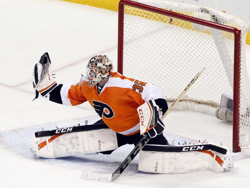 Philadelphia Flyers' Steve Mason makes a glove save of a shot on goal during the third period of an NHL hockey game against the Detroit Red Wings, Tuesday, Jan. 28, 2014, in Philadelphia. The Flyers won 5-0. (AP Photo/Tom Mihalek)