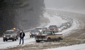 Vehicles are backed up on a snow covered US Highway 280 during a snow storm, Tuesday, Jan. 28,  2014 in Chelsea, Ala. A fast-moving, unexpectedly severe winter storm blanketed much of Alabama with a treacherous layer of frozen precipitation Tuesday, causing multiple wrecks, stranding hundreds of children in schools and coating palm trees with ice at the beach.  (AP Photo/Hal Yeager)