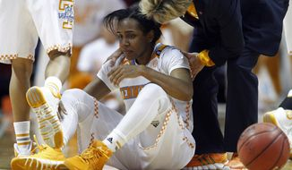 Tennessee guard Ariel Massengale (5) is assisted by head coach Holly Warlick after being injured in the first half of an NCAA college basketball game Thursday, Jan. 23, 2014, in Knoxville, Tenn. Massengale didn't return to the game after getting hit in the face while making a steal late in the first half. No. 11 Tennessee defeated Florida 89-69. (AP Photo/Wade Payne)