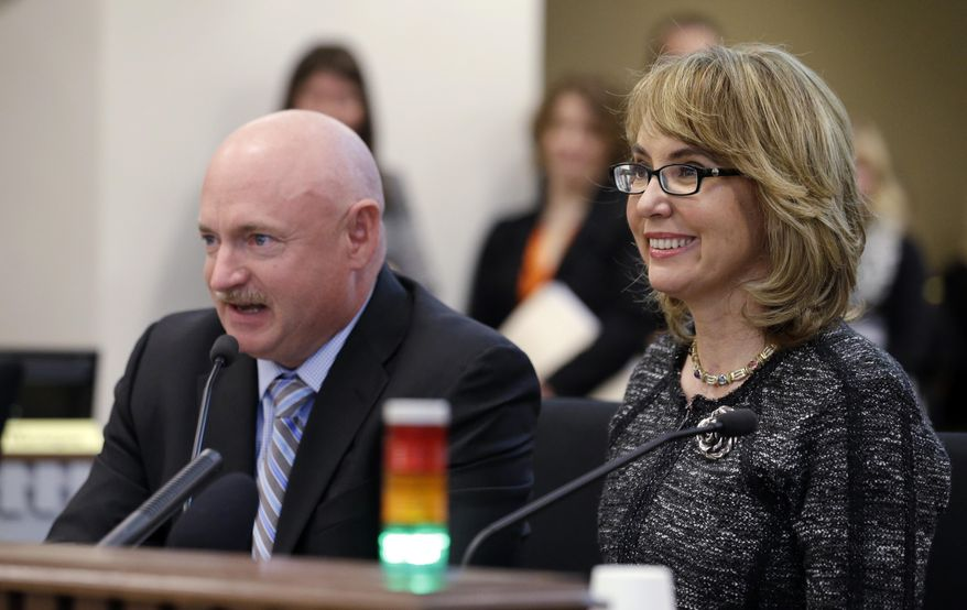 """Former Arizona Congresswoman Gabrielle Giffords, right, smiles briefly as her husband, retired NASA space shuttle commander Mark Kelly, testifies before a Washington state House panel Tuesday, Jan. 28, 2014, in Olympia, Wash. Giffords, who survived a 2011 shooting, testified before the panel considering an initiative to expand firearm background checks in the state, telling lawmakers that """"the nation is counting on you."""" With Kelly sitting next to her, Giffords spoke slowly and briefly to the panel that was taking public testimony on Initiative 594. (AP Photo/Elaine Thompson)"""