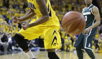 Iowa guard Devyn Marble, left, reacts in front of Michigan State guard Alvin Ellis III, right, after being called for a foul during the first half of an NCAA college basketball game, Tuesday, Jan. 28, 2014, in Iowa City, Iowa. (AP Photo/Charlie Neibergall)
