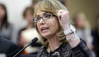 "Former Arizona Congresswoman Gabrielle Giffords pumps her fist as she testifies before a Washington state House panel Tuesday, Jan. 28, 2014, in Olympia, Wash. Giffords, who survived a 2011 shooting, testified before the panel considering an initiative to expand firearm background checks in the state, telling lawmakers that ""the nation is counting on you."" With her husband, retired NASA space shuttle commander Mark Kelly sitting next to her, Giffords spoke slowly and briefly to the panel that was taking public testimony on Initiative 594. (AP Photo/Elaine Thompson)"