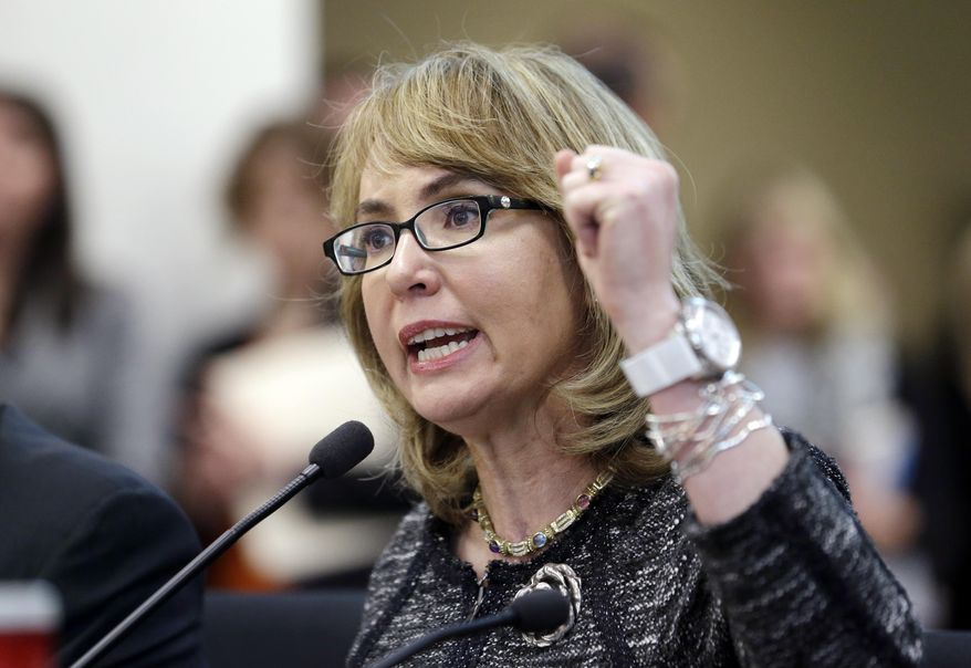 """Former Arizona Congresswoman Gabrielle Giffords pumps her fist as she testifies before a Washington state House panel Tuesday, Jan. 28, 2014, in Olympia, Wash. Giffords, who survived a 2011 shooting, testified before the panel considering an initiative to expand firearm background checks in the state, telling lawmakers that """"the nation is counting on you."""" With her husband, retired NASA space shuttle commander Mark Kelly sitting next to her, Giffords spoke slowly and briefly to the panel that was taking public testimony on Initiative 594. (AP Photo/Elaine Thompson)"""