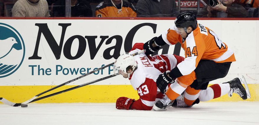 Philadelphia Flyers' Kimmo Timonen, right, rides Detroit Red Wings' Darren Helm down to the ice as they chase the puck during the first period of an NHL hockey game, Tuesday, Jan. 28, 2014, in Philadelphia.  (AP Photo/Tom Mihalek)