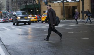 A pedestrian moves quickly outside of a crosswalk at the busy intersection of W. 96th Street and Broadway in the Upper West Side of New York Monday, Jan. 27, 2014. Although it appears clear sometimes at this intersection, cars using turning lanes can quickly encroach on non-crosswalk areas. New York Mayor Bill de Blasio, in the wake of 11 pedestrian deaths in the city already in 2014, is taking direct aim at not just drivers but pedestrians, with a crackdown that has resulted in the first jaywalking tickets some residents have ever seen. (AP Photo/Craig Ruttle)