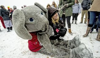 Shannon Moen grabs a photo with University of Alabama mascot  Big Al as he made an appearance on the Quad as snow fell Tuesday, Jan. 28, 2014 in Tuscaloosa, Ala. A winter storm that would probably be no big deal in the North all but paralyzed the Deep South on Tuesday, bringing snow, ice and teeth-chattering cold, with temperatures in the teens in some places. (AP Photo/AL.com, Vasha Hunt) MAGS OUT