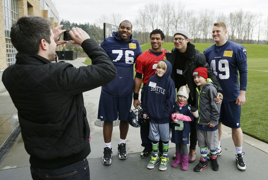 Seattle Seahawks NFL football quarterback Russell Wilson, third from upper right, poses for a photo Thursday, Jan. 2, 2014, with Judah Smith, second from upper right, pastor of The City Church, and other guests following practice in Renton, Wash. (AP Photo/Ted S. Warren)