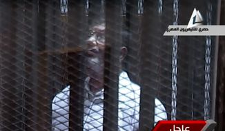 In this image taken from Egyptian state TV, toppled President Mohammed Morsi stands inside a glass-encased metal cage in a courtroom in Cairo, Tuesday, Jan. 28. 2014. Morsi was separated from other defendants for the start of a new trial Tuesday over charges from prison breaks during the country's 2011 revolution. (AP Photo/Egyptian State TV)